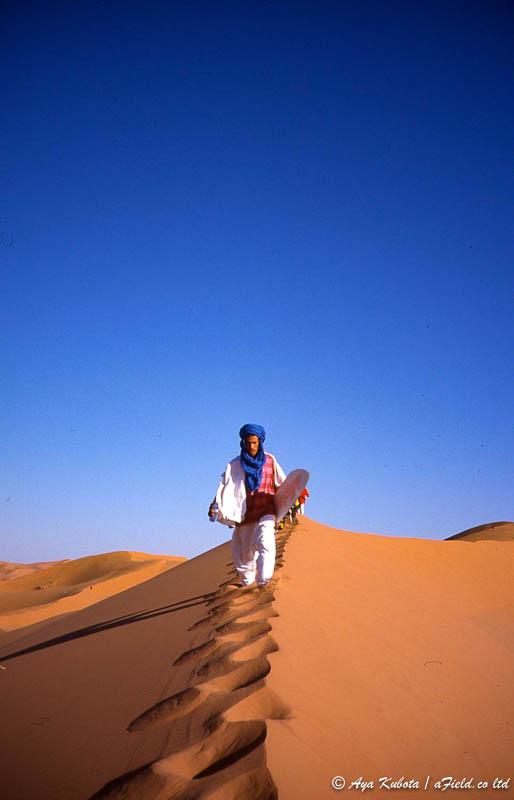 サハラ砂漠の案内人、イブラハム。ヨーロッパ人のスノーボーダーがおいていったスノーボードを持っていた